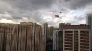 On Singapore's National Day, 9 August 2014, helicopters fly the flag toward the National Day Parade.